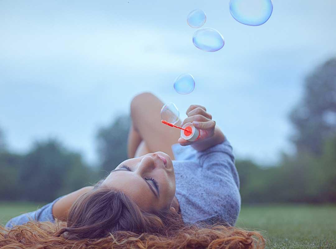 jong vrouw blaast zeepbellen